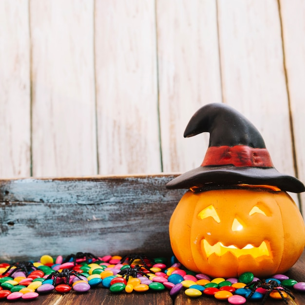 Jack-o-lantern in witch hat and candies Free Photo