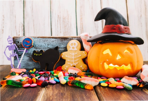 Jack-o-lantern in witch hat and halloween sweets Free Photo