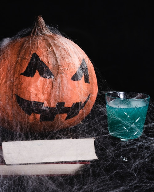 Jack-o'-lantern with spiderweb and drink Free Photo