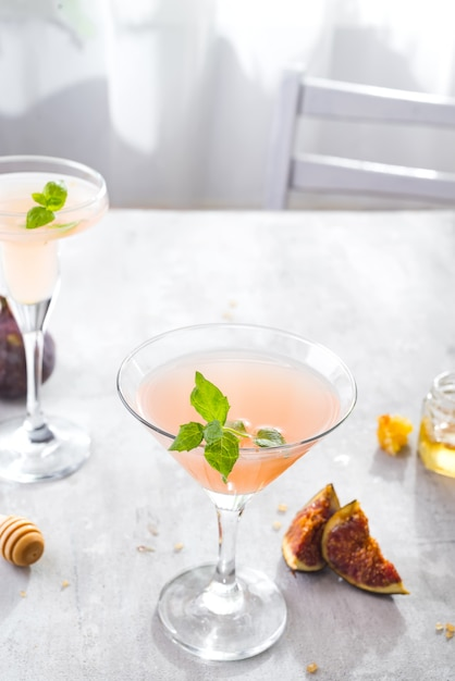 Jack rose cocktail with figs and honey on light background over windows, flat lay with copy space Premium Photo