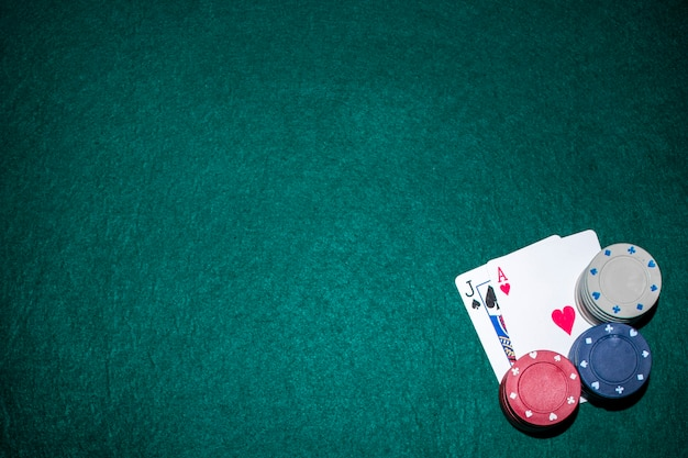 Jack of spade and heart ace card with casino chip stack on green poker table Free Photo