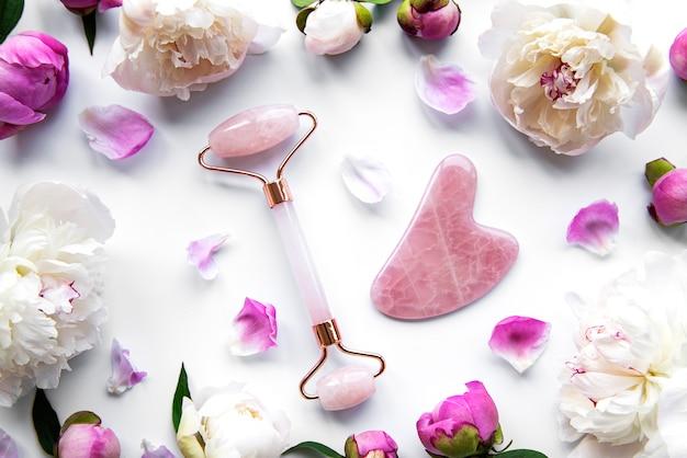 美容フェイシャルマッサージセラピーとピンクの牡丹のための翡翠フェイスローラー。白い表面に平らに置く Premium写真