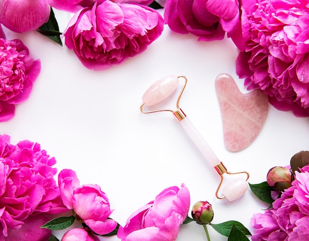 美容フェイシャルマッサージセラピーとピンクの牡丹のための翡翠のフェイスローラー。 Premium写真