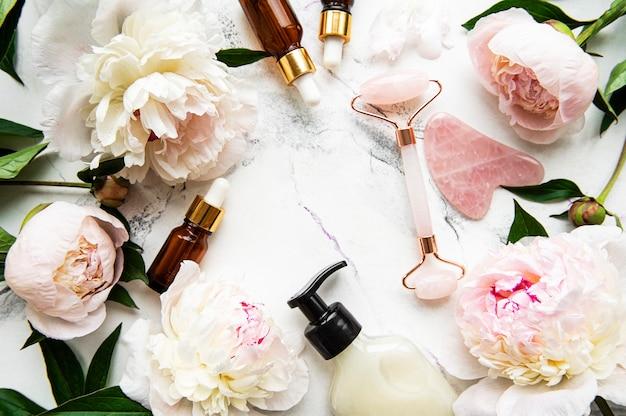 美容フェイシャルマッサージセラピー、マッサージオイル、ピンクの牡丹用のジェイドフェイスローラー。白い大理石の表面に平らに置く Premium写真