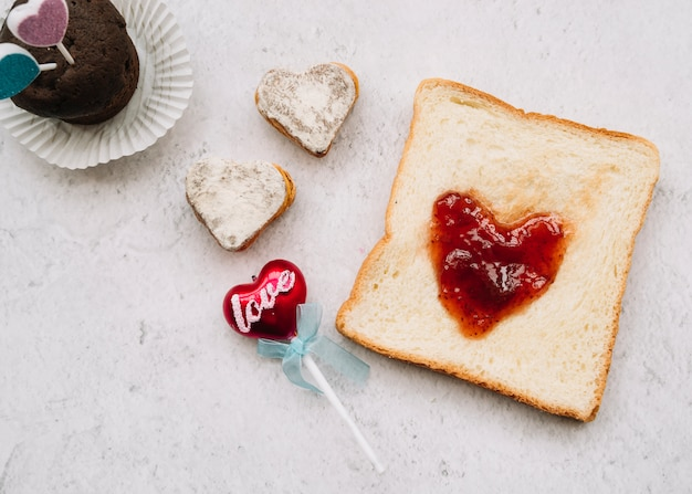 Jam in shape of heart on toast with sweets Free Photo