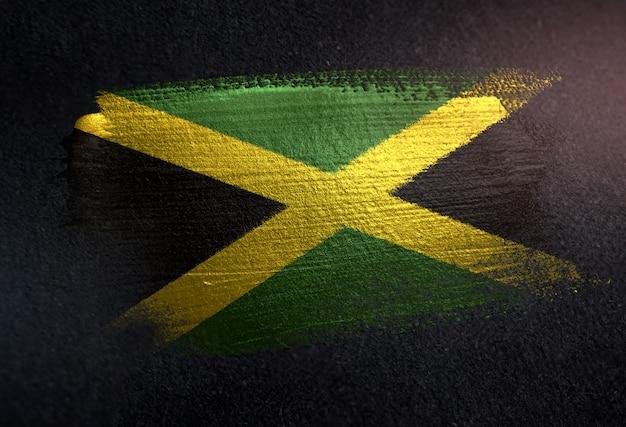 Jamaica flag made of metallic brush paint on grunge dark wall Premium Photo