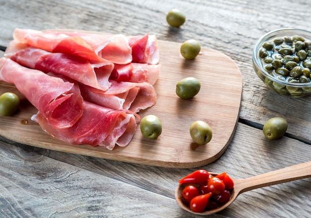 Jamon with capers and olives on the wooden board Premium Photo