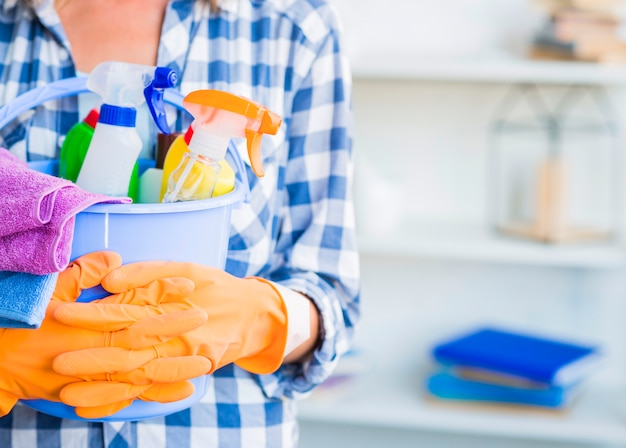Janitor holding cleaning equipments in bucket Free Photo
