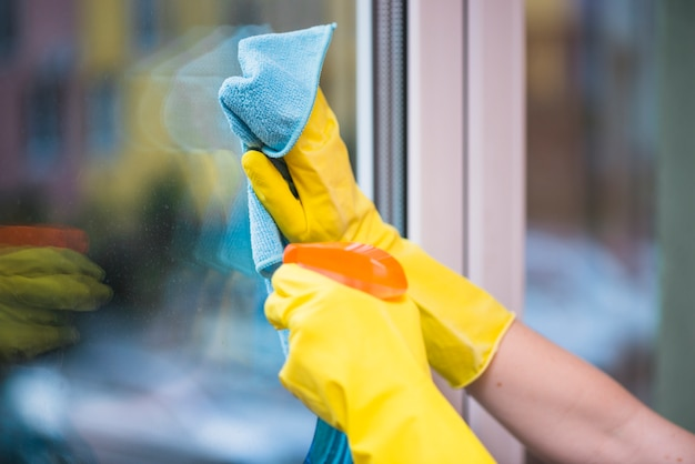 Janitor's hand cleaning glass window with cloth Free Photo