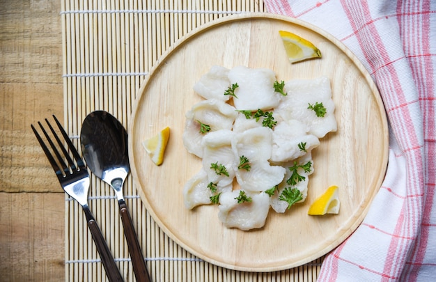 Japanese cooked fish fillet piece with lemon and spices on wooden tray on dining table Premium Photo