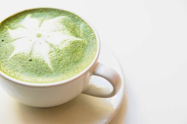Japanese green tea latte in white cup against white background Free Photo