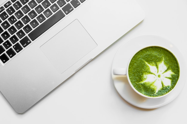 Japanese green tea latte in white cup near the laptop on white desk Free Photo