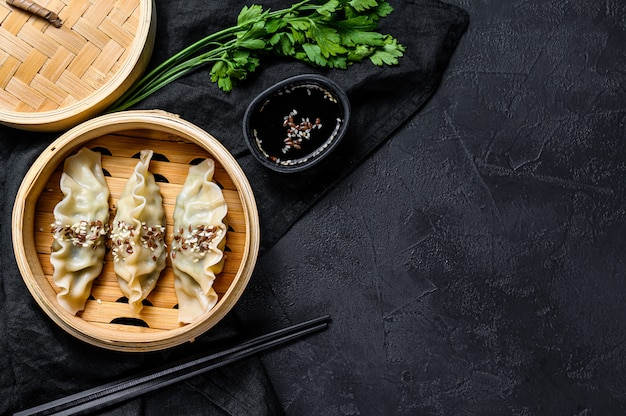 Japanese gyoza in a traditional bamboo steamer. top view. space for text. rustic old vintage black background Premium Photo