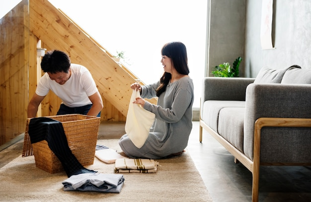 Japanese husband and wife folding clothes together Free Photo