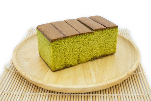 Japanese matcha green tea cake cheesecake on wooden plate and traditional mat isolated Premium Photo
