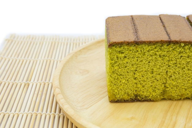 Japanese matcha green tea cake cheesecake on wooden plate and traditional mat Premium Photo