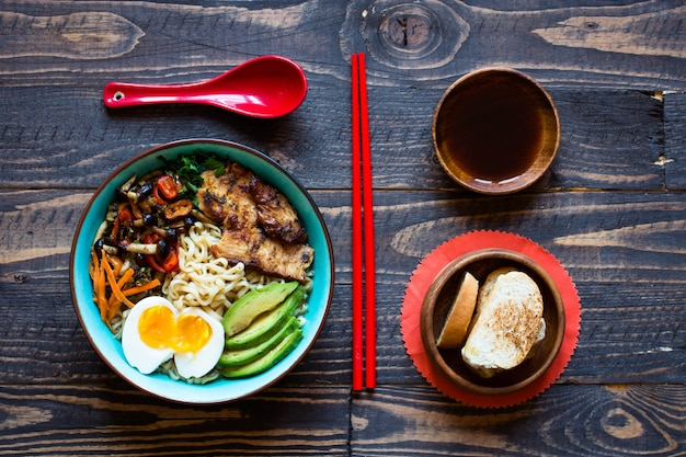 Japanese noodles bowl with chicken, carrots, avocado Premium Photo