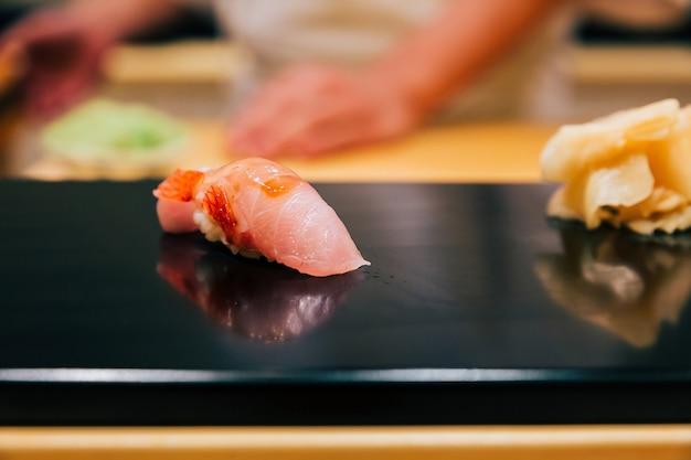 Japanese omakase in edo style close up otoro (fatty tuna) sushi served on glossy black plate. Premium Photo