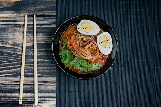 Japanese ramen with seafood, herbs and pickled eggs on a dark surface Premium Photo