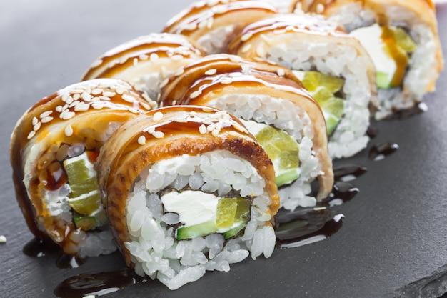Japanese restaurant, sushi roll on black slate plate. Premium Photo
