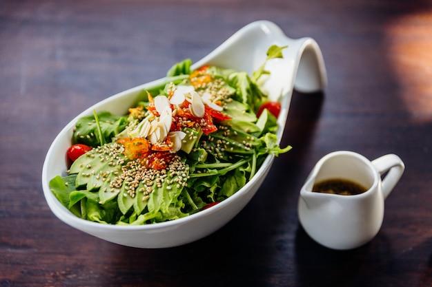 Japanese salad with avocado, tomato, green oak, almond and sesame topping sesame salad dressing. Premium Photo