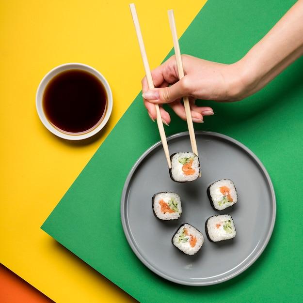 Japanese sushi dish and hand holding chopsticks Free Photo