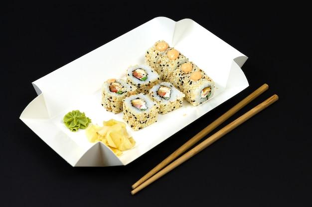暗い背景に白いエコ紙使い捨てボックスで日本の寿司ロール Premium写真