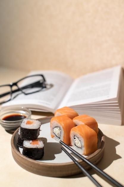 ライトプレート、ベージュの背景で提供される日本の巻き寿司。本と昼食。ホームリラックスコンセプト Premium写真