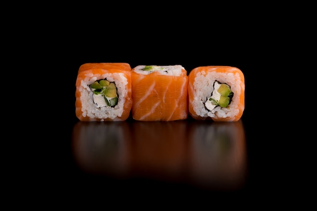 Japanese traditional food - sushi with avocado, rice, cottage cheese, salmon and green onion Premium Photo