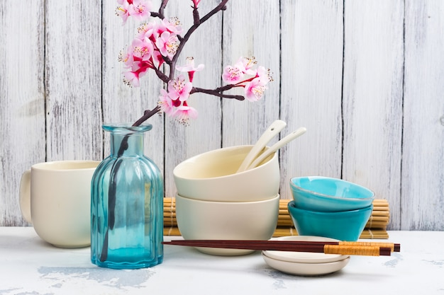 Japanese utensils, dinnerware, chopsticks and branch of blooming sakura on white asian background Premium Photo