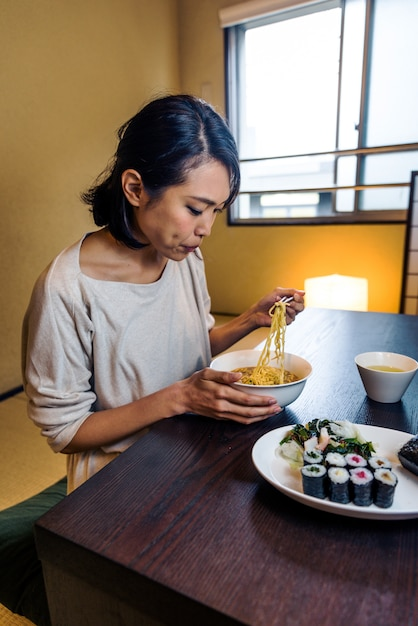 Japanese woman eating in a traditional apartment Premium Photo