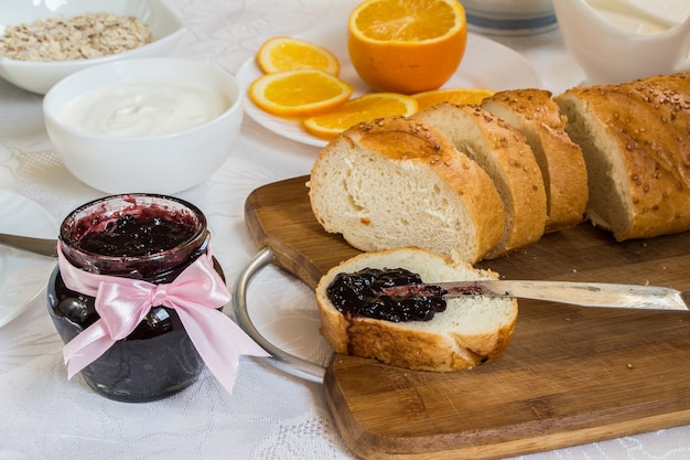 Jar of currant jam on table with loaf of bread Free Photo