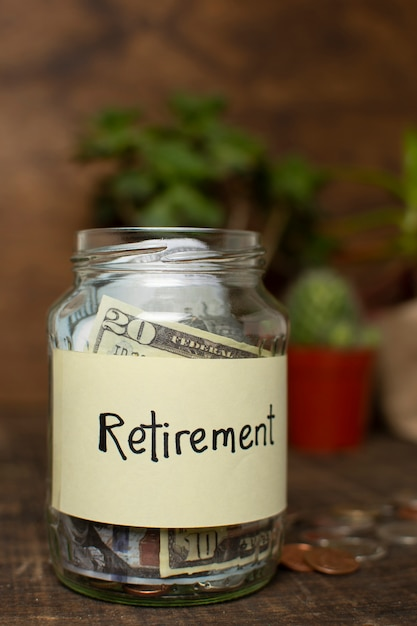 Jar filled with money and retirement label Free Photo