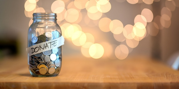 Jar full of coins for donation Premium Photo