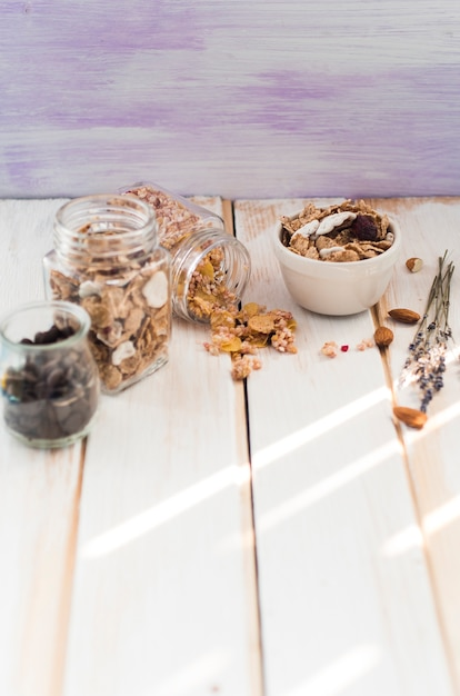 Jar of granola; cornflakes and chocolate chips near dry fruits on wooden surface Free Photo