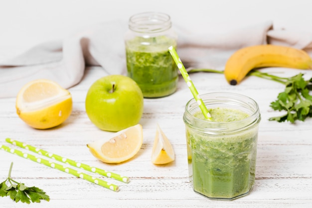 Jar of healthy smoothie with apple and lemon slices Free Photo