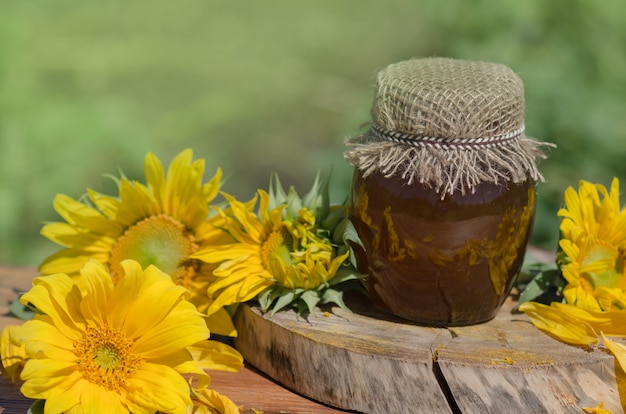 Jar of honey and sunflowers on wooden table over bokeh garden background Premium Photo