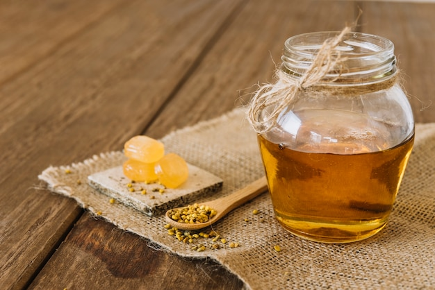 Jar of honey with bee pollen seeds and candies on sack cloth Free Photo