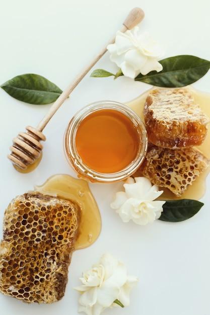 Un vasetto di miele con fiori intorno Foto Gratuite