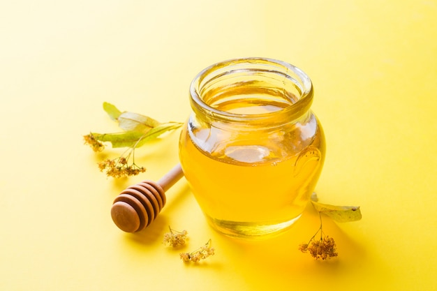 A jar of liquid honey from linden flowers and a stick with honey on yellow surface. copy space Premium Photo