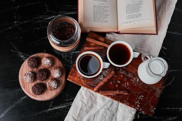 Barattolo di latte con tazzine da caffè e biscotti Foto Gratuite