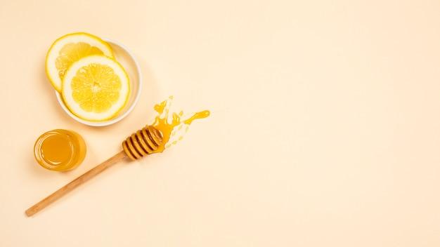 健康な蜂蜜の瓶と無地の表面に蜂蜜ディッパーのレモンスライス Premium写真