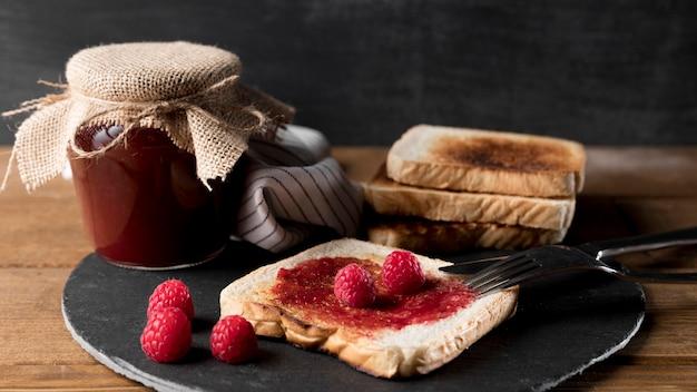 Vasetto di marmellata di lamponi con pane e coltello Foto Gratuite