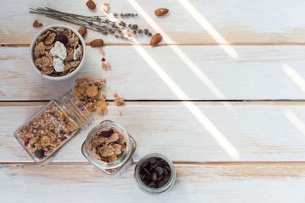 Jar of spilled granola near cornflakes; dry fruits and chocolate chips on wooden plank Free Photo
