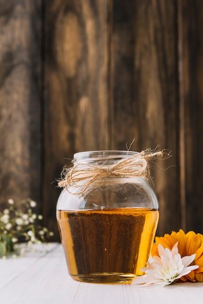 Jar of sweet honey and flowers on desk Free Photo