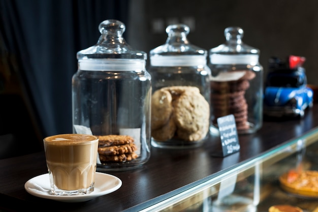 Jar of various cookies with latte coffee cup on cafe counter Free Photo