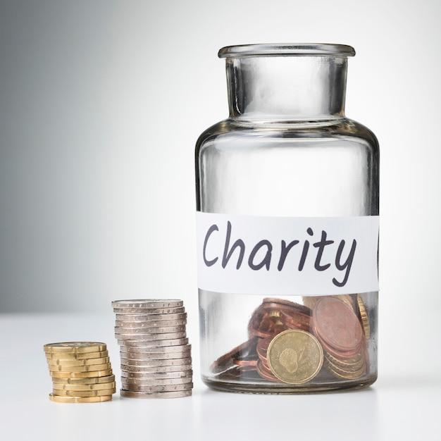 Баночка с монетами и стопками сбережений на столе Бесплатные Фотографии