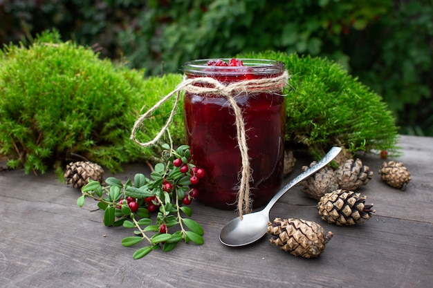 Jar with lingonberry jam on an old wooden table, still life Premium Photo