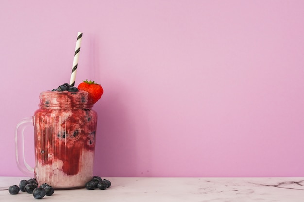 Jar with strawberry and blueberries smoothie with straw Free Photo