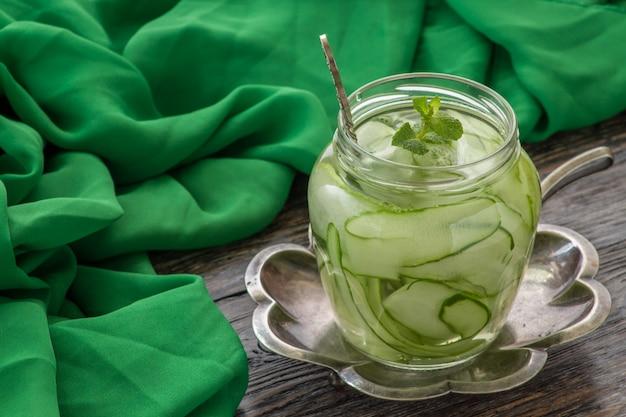 Jar with tasty cucumber lemonade on wooden table Premium Photo